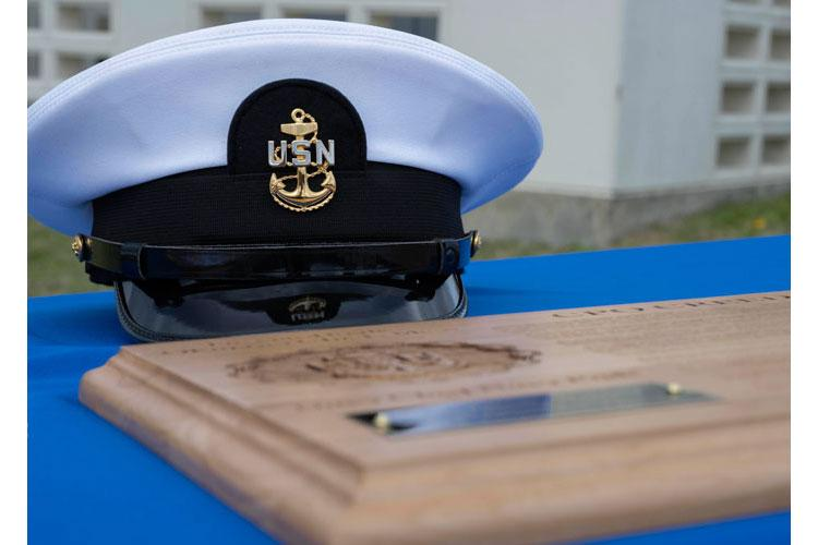 WHITE BEACH, Japan (Jan. 29, 2021) A navy chief petty officer combination cover rests on a table with Chief's Creed plaques during a chief pinning ceremony held onboard Commander, Fleet Activities Okinawa White Beach Naval Facility Jan. 29, 2021. The ceremony pinned or honored six Sailors and one U.S. Air Force Airman. (U.S. Navy photo by Mass Communication Specialist 1st Class David R. Krigbaum)