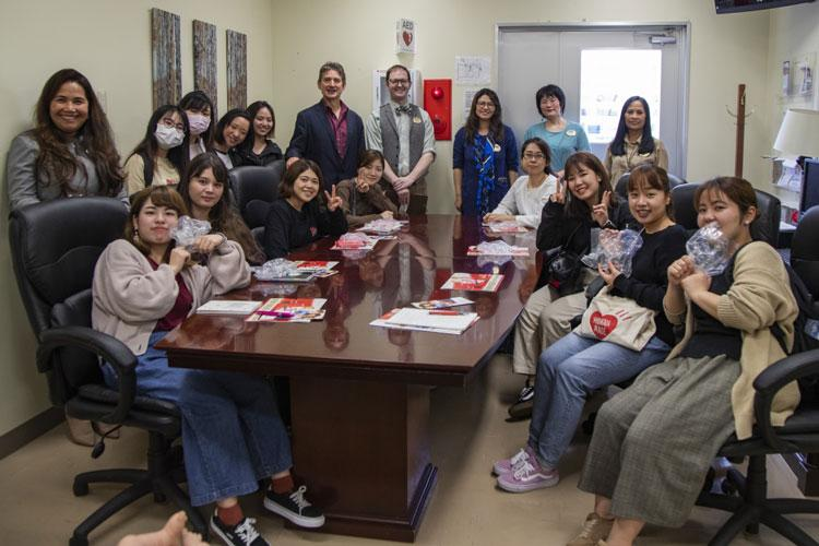 Okinawa University students pose for a photo with a variety of behavioral health professionals and social workers from the Behavioral Health Center, Feb. 13, 2020, on Camp Foster. Students were given the opportunity to meet and greet with substance abuse clinicians, family advocacy workers and community counseling programs. (U.S. Marine Corps photo by Lance Cpl. Karis Mattingly)