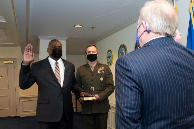 Washington Headquarters Services Director Thomas Muir, left, swears in Lloyd J. Austin III as secretary of defense at the Pentagon, Jan. 22, 2021. Holding the Bible is Marine Corps Lt. Col. Caleb Hyatt, the junior military assistant to the secretary of defense. Austin is the first African-American to lead the Defense Department.