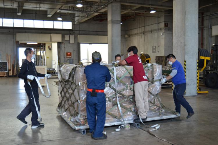 A team of aircraft services specialists working with the 733rd Air Mobility Squadron on Kadena Air Base, Okinawa, secures a pallet of Burger King buns for transport headed to Andersen Air Force Base, Guam. Due to unseen circumstances, the American Bakery in Guam could not deliver their obligated buns supply to all of the Burger King restaurants on the island, to include the one on Andersen AFB, which caused a ripple effect within the Exchange. (U.S. Army Photo by Staff Sgt. Mark A. Kauffman)