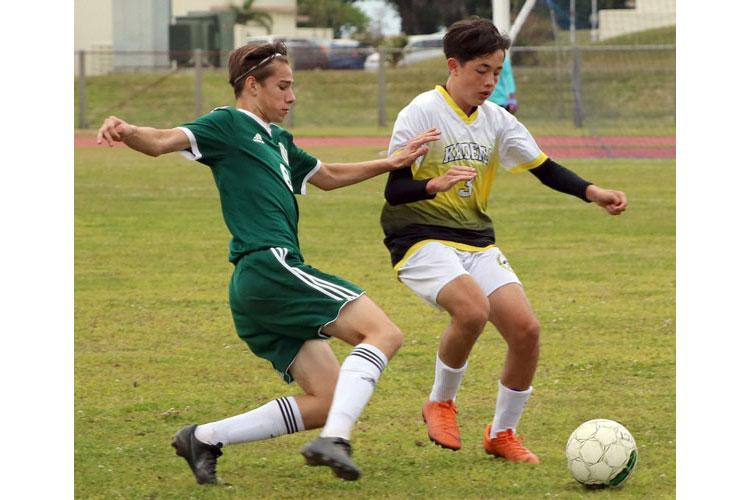 Kubasaki's Angelo Medieros and Kadena's Nolan Taylor scrap for the ball during Wednesday's Okinawa boys soccer match. (JAELYN FORBES/SPECIAL TO STRIPES)