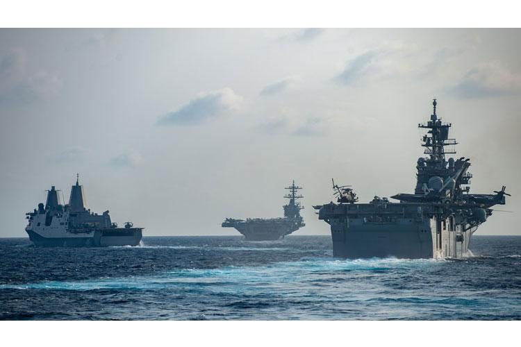 SOUTH CHINA SEA (March 15, 2020) Ships from the Theodore Roosevelt Carrier Strike Group and the America Expeditionary Strike Group transit the South China Sea, March 15, 2020. (Photo by Mass Communication Specialist 3rd Class Nicholas V. Huynh)