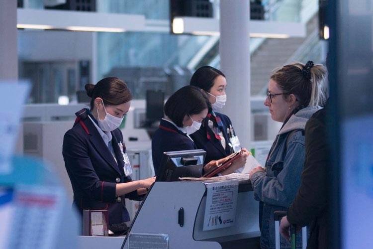 An airline employee helps a customer check in for a flight out of Haneda International Airport in Tokyo, March 18, 2020. (AKIFUMI ISHIKAWA/STARS AND STRIPES)