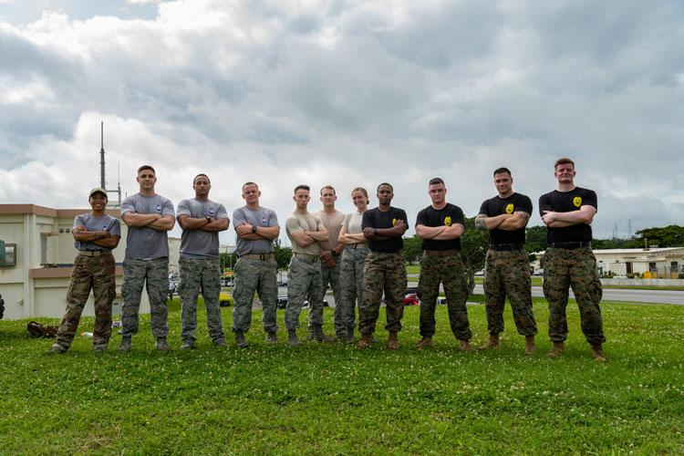U.S. Air Force and U.S. Marine Corps teams pose for a photo after the Shogun Challenge for the 2019 Police Week May 14, on Kadena Air Base, Japan. Each team consisted of four members from the 18th Security Forces Squadron, the First Sergeants' Association, and the Provost Marshal's Office, who competed in events such as weapons assembly, ammo can runs, and memory work. (U.S. Air Force photo by Airman 1st Class Cynthia Belío)