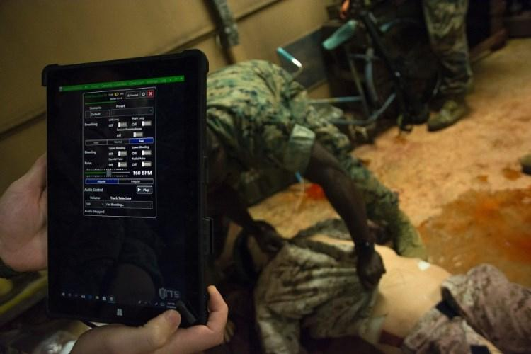 An instructor uses a tablet to control the breathing, pulse and noises of a simulated casualty dummy using a tablet during training at Camp Hansen, Okinawa, Thursday, July 11, 2019. (CARLOS VAZQUEZ/STARS AND STRIPES)