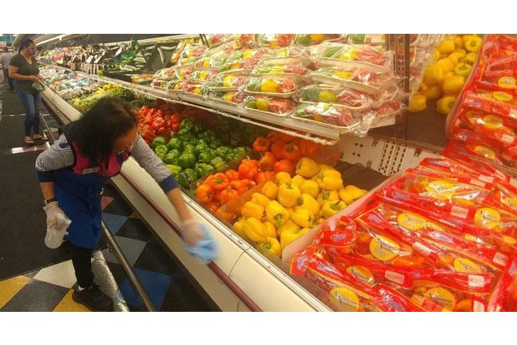 At Marine Corps Base Camp Pendleton, California, Commissary, store associate Nora Gabuat sanitizes a produce display case to ensure preventive measures are followed. (DeCA photo: Robert Lunetta)