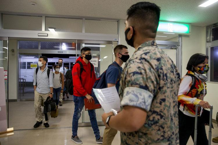 U.S. Marines Corps Lance Cpl. Jonathan Paschal, a driver within the Joint Reception Center (JRC) welcomes the new Marines to the island of Okinawa on Kadena Air Base, July 9, 2020. The JRC staff drive to Kadena Air Base to transport the Marines and greenside sailors to the barracks to execute a 14-day restriction of movement (ROM), followed by a week of welcome aboard classes to orient them to the new island. (U.S. Marine Corps photo by Lance Cpl. Karis Mattingly)