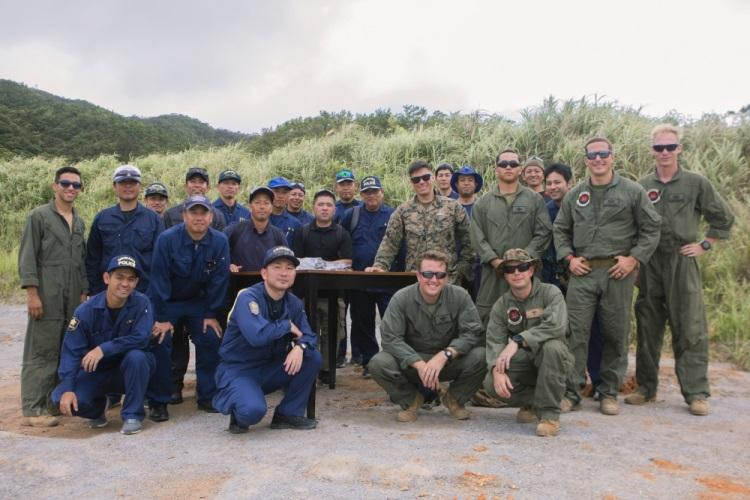 Explosive Ordnance Disposal technicians with Headquarters and Support Battalion, Marine Corps Installations Pacific, and members of Okinawa's Prefectural Police Department pose for a photo following bilateral post-blast investigation training on Camp Hansen, Okinawa, Japan, July 17, 2019. The training was conducted to instruct members of Okinawa's Prefectural Police Department proper procedure to approach, investigate, and examine a scene following an IED detonation. (Photo by Cpl. Christopher A. Madero)