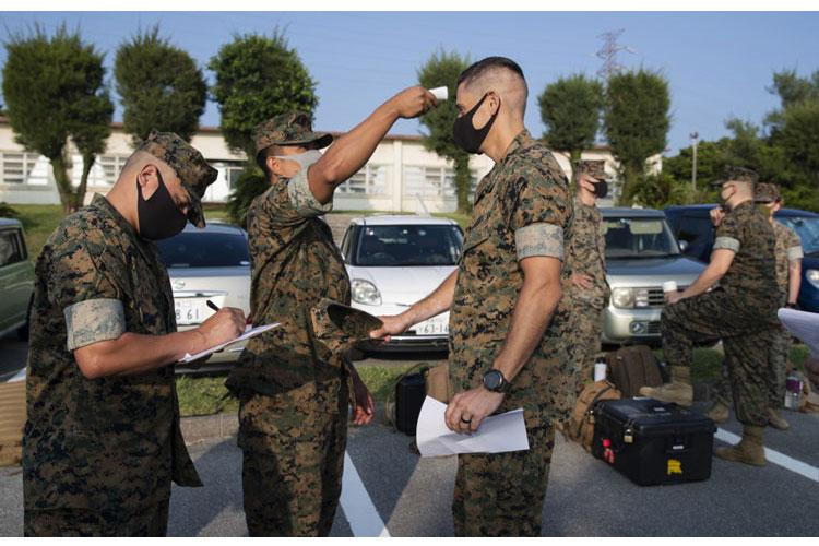 U.S. Marines with 3d Marine Expeditionary Brigade get their temperature checked before a flyaway drill at Camp Courtney, Okinawa, Japan, Aug. 18, 2020. (U.S. Marine Corps photo by Lance Cpl. Hannah Hall)