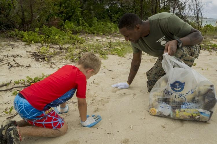 U.S. Navy Petty Officer 3rd Class Andrew Fraser searches the sand for trash during a beach cleanup on Igei Beach, August 22, 2019. A beach cleanup is held periodically and is part of Camp Hansen's USO Learning, Engaging, Activity, and Play program. The LEAP program provides service members the opportunity to volunteer in community oriented activities. Fraser, a native of Queens, New York, is a corpsman with Combat Logistics Battalion 31. (U.S. Marine Corps photo by Lance Cpl. Kindo Go)