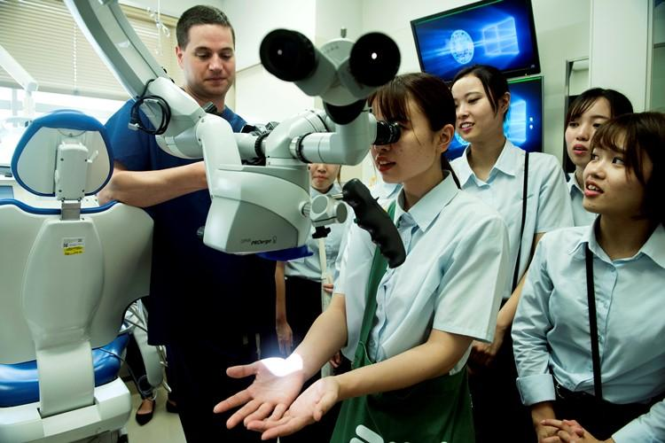 Maj. David Weyh, 18th Dental Squadron endodontist, shows off a dental microscope used for root canal procedures and surgeries to Miyu Nakamura, a dental hygienist student, during White Dental Clinic's tour of the 18th DS clinic, Aug. 16, 2019. The microscope is a staple piece of equipment for endodontists, who use this asset for complex root canal procedures and more. The tour took place for students to learn about the unique capabilites of the clinic at Kadena.