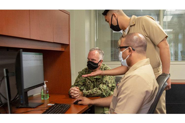 Navy Capt. Bradford Smith (left), commanding officer of Naval Medical Center San Diego, enrolls in MHS GENESIS with the help of training coordinators Navy Lt. Donny Le (standing) and Navy Petty Officer 2nd Class Terrance Stevens. (Photo by Petty Officer 3rd Class Jake Greenberg)