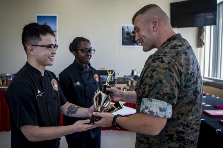 U.S. Marine Corps Lt. Col. Michael Hlad, right, presents trophies to the winners of the 2019 Chef of the 4th Quarter competition, Cpl. Tommy Pham, left, and Cpl. Jaden Brown, at Camp Hansen, Okinawa, Japan, Sept. 26, 2019. Pham, a native of Broussard, La., is a food service specialist with, 1st Battalion, 12th Marine Regiment. Brown, a native of Washington D.C., is a food service specialist with 3rd Battalion, 12th Marine Regiment. (U.S. Marine Corps photo by Lance Cpl. Kindo Go)
