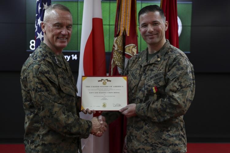 Lt. Gen. H. Stacy Clardy, III Marine Expeditionary Force Commanding General presents an award to Maj. William Easter, the theatre security cooperation officer with III MEF, in the Battle Cabin room of the III MEF headquarters building, Camp Courtney, Okinawa, Japan, Feb. 14, 2020. Easter was awarded the Navy and Marine Corps medal for saving the life of a drowning pregnant woman. (U.S. Marine Corps photo by Lance Cpl. Hannah Hall)