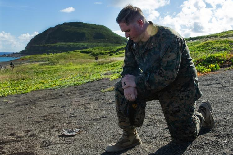 U.S. Navy Lt. Hal Jones prays at the base of Mt. Suribachi, Japan, July 2, 2019. Jones, the Navy Chaplain of 7th Communication Battalion, spoke with the Marines and Sailors and did a moment of silence to honor the service members that died in the Battle of Iwo Jima. (U.S. Marine Corps photo by Lance Cpl. Brienna Tuck)