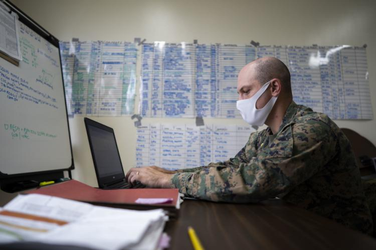 U.S. Marine Corps Maj. Gregory Procaccini, the Joint COVID-19 Response Center Liaison Element officer in-charge with the COVID Cell, drafts an email at the Public Health & Behavioral Health center, Camp Foster, Okinawa, Japan Dec. 2, 2020. The COVID Cell is one of three active organizations, along with the Joint COVID-19 Response Center and Task Force Safeguard, in combating the spread of COVID-19 among Status of Forces Agreement personnel on Okinawa. (U.S. Marine Corps photo by Cpl. Ryan H. Pulliam)