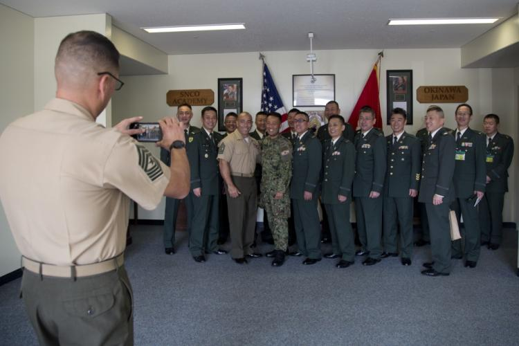 U.S Marine Corps Sgt.Maj. Michael S. Payne, Staff Non-Commissioned Officer Academy Director takes a group photo of Master Gunnery Sgt. Jose C. Rios, Staff Non-Commissioned Officer Academy Deputy Director with the Japanese Ground Self- Defense Force command sergeants major course on Camp Hansen, Okinawa, Japan, Jan 30, 2019. The annual visit is held to educate JGSDF CSMC about Marine Corps military education and discuss common challenges senior leaders encounter. (Photo by Lance Cpl. Krysten I. Gomez)