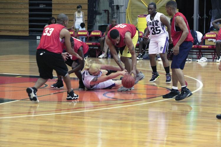 Players with the Lady Kings and 1-1, in the white and red jerseys respectively, scramble for a loose ball during Southern Basketball League play at Gunners Fitness Center on Camp Foster Aug. 30. The league started Aug. 30 and will last until Oct. 13. 1-1, an Army team, won the game.