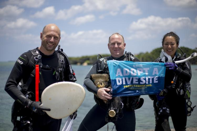 Divers pose for a photo with some of the trash they found during a scuba beach cleanup May 26, 2019 at Sunabe North Steps, Okinawa, Japan. The cleanup raised awareness of the oceans condition as well as showed divers the impact they can make by picking up trash that has made its way to the water. Divers surfaced with their bags filled with soda cans, plastic bottles, fishing line, even a car battery and toilet seat were recovered from the ocean floor. (U.S. Marine Corps photo by Lance Cpl. Nicole Rogge)