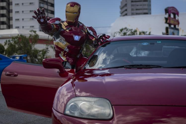 A car show attendee dressed as popular superhero, Iron Man, poses for a photo during the 2nd annual United Service Organizations Okinawa car show on Camp Foster, Okinawa, Japan, September 14, 2019. The car show helped strengthen relationships between local residents and members of the U.S. community through a public automobile exhibition. (U.S. Marine Corps photo by Lance Cpl. Kindo Go)