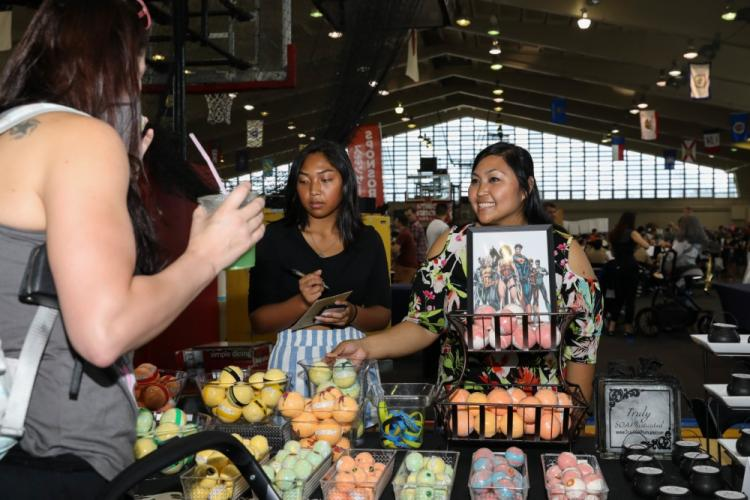 Gina Ferrer, right, a family medicine nurse with U.S. Naval Hospital Okinawa, and her daughter greet attendees at Camp Foster Fieldhouse during Comic Con Okinawa, Japan, Oct. 13, 2019. This annual event began in 2011 and is catered to comic book fans, movie fans, artists, and video gamers to meet and greet with comic industry professionals and celebrities.The event was open to members of the U.S. and local communities. (U.S. Marine Corps photo by Cpl. Kayla V. Staten)