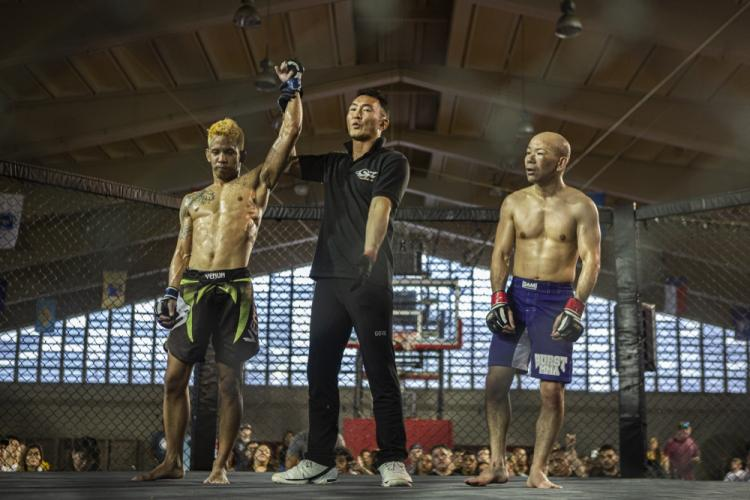 Kenji Arakaki, left, a member of the local Okinawa community, claims victory during a mixed martial arts event at Camp Foster's field house, Feb. 15, 2019. The event promoted healthy competition between international fighters; building relationships between the U.S. military and international communities through sportsmanship and mutual respect. (U.S Marine Corps Photo by Cpl. Christopher Madero)