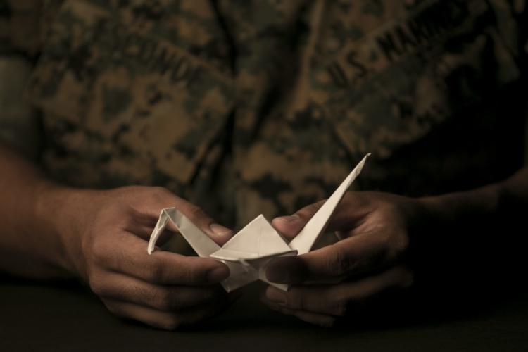 Staff Sgt. Ismael Esconde, the substance abuse control officer with Headquarters and Service Company, 3rd Battalion, 3rd Marine Regiment, holds a crane he folded at building 267 aboard Marine Corps Base Hawaii April 19, 2017. Esconde uses origami as a way to make a positive impact in his local community. (U.S. Marine Corps photo by Sgt. Brittney Vella)