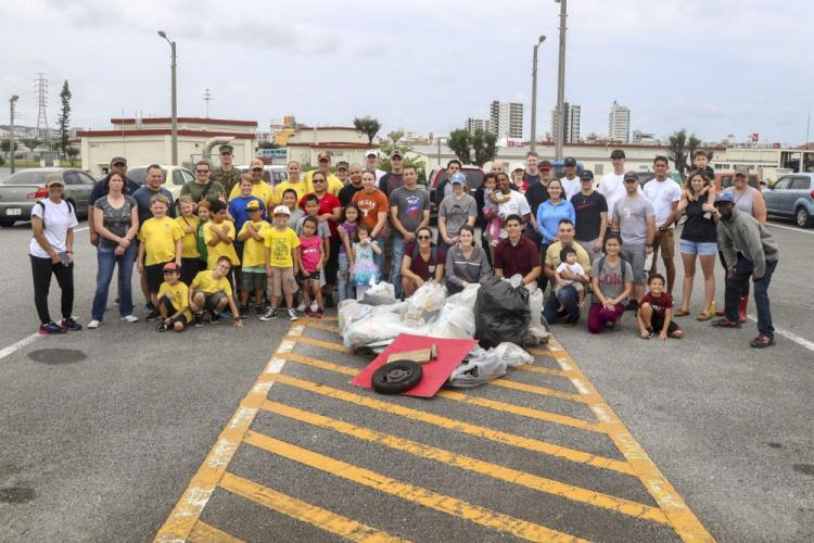 U.S. service members and their families pose for a group photo with collected trash near Camp Fpterr, April 20, 2019. The trash was collected in support of the Earth Day perimeter clean up hosted by Headquarters and Support Battalion, Marine Corps Installations Pacific, Marine Corps Base, Camp Smedley D. Butler. (U.S. Marine Corps photo by Lance Cpl. Savannah Mesimer)