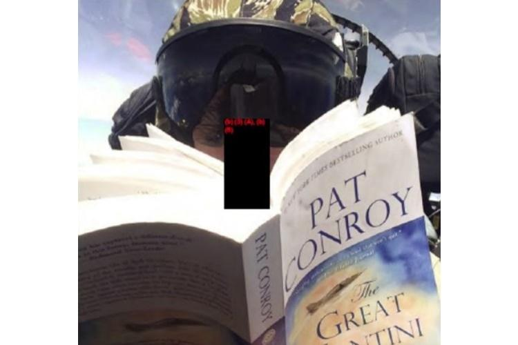 """An aviator with Marine All-Weather Fighter Attack Squadron 242 at Marine Corps Air Station Iwakuni, Japan, reads """"The Great Santini"""" by Pat Conroy in an in-flight photo included with a report into a midair collision off Japan in December 2018. (U.S. MARINE CORPS)"""
