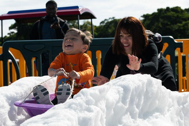 A woman pushes a child on a snow sled during the 18th Wing Tinsel Town event at Kadena Air Base, Japan, Dec. 14, 2019. Other events and games included a rock climbing wall, food trucks, and more. (U.S. Air Force photo by Senior Airman Matthew Seefeldt)
