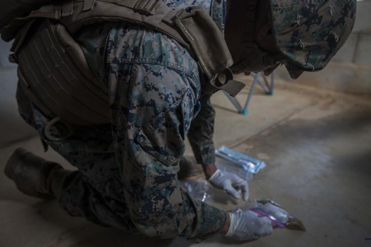 U.S. Marine Cpl. Carlos Ramos gathers forensic material during tactical site exploitation training at Combat Town, Okinawa, Japan, Sept. 12, 2018. Marine Corps Systems Command's Identity Operations Team is working to enhance the Expeditionary Forensics Exploitation Capability, which is used to differentiate between friend or foe on the battlefield. (U.S. Marine Corps photo by Pfc. Kindo Go)