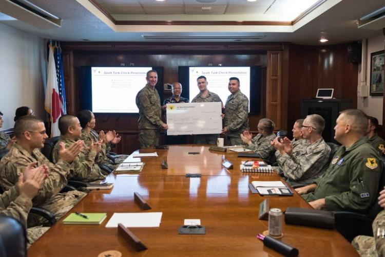 U.S. Air Force Brig. Gen. Case A. Cunningham, 18th Wing commander, presents a check for $2,500 to the 2018 Shogun Spark Tank winners for their contingency lodging application, LodgeNET, on Feb. 11, 2019 at Kadena Air Base, Japan. Innovative incentive programs such as the 18th WG Spark Tank encourage Airmen to think outside the box and provide new solutions to everyday problems. (U.S. Air Force photo by Airman 1st Class Cynthia Belío)