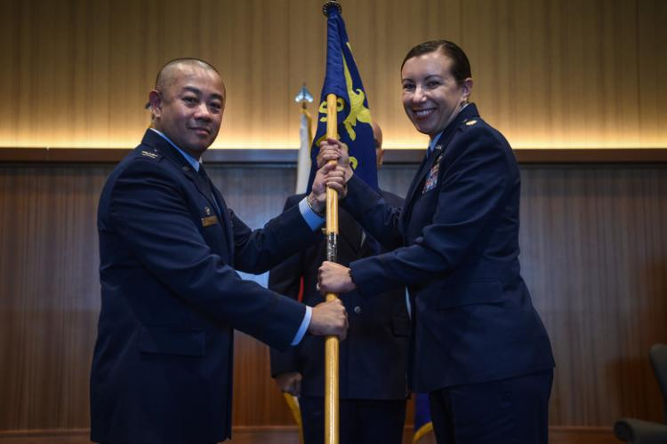 U.S. Air Force Col. Thang T. Doan, 18th Mission Support Group commander, passes the 718th Force Support Squadron guideon to Maj. Jama Stillwell, 718th FSS commander, during the 718th FSS activation ceremony at Kadena Air Base, July 16,th 2019. (U.S. Air Force photo by Senior Airman Kristan Campbell)