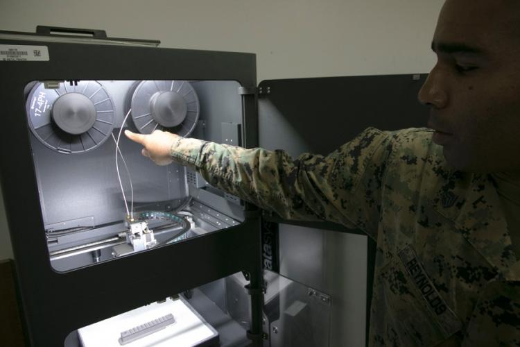 Marine Staff Sgt. Quincy Reynolds of the III Marine Expeditionary Force's 3rd Maintenance Battalion shows off the unit's new Markforged Metal X 3D printer at Camp Kinser, Okinawa, Jan. 16, 2020. MATTHEW M. BURKE/STARS AND STRIPES