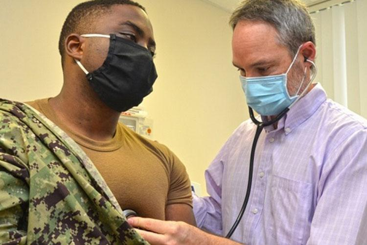 Michael Service, a family nurse practitioner at Naval Branch Health Clinic Jacksonville, checks Navy Petty Officer 3rd Class Gabriel Upunda's heart in September 2020 (Photo by: Jacob Sippel, Naval Hospital Jacksonville).