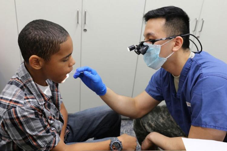 Jordyn Pafford, sixth grader, receives a dental screening conducted by Capt. James Lee, a general dentist. (U.S. Army photo by Lance D. Davis)