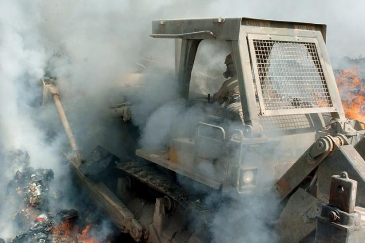 In a 2004 photo, smoke billows in from all sides as Sgt. Richard Ganske, 84th Combat Engineer Battalion, pushes a bulldozer deep into the flames of a burn pit at LSA Anaconda, Iraq. U.S. ARMY