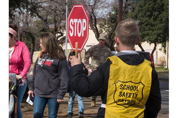 A crossing guard stops traffic for students near Joan K. Mendel Elementary School at Yokota Air Base, Japan, Friday, Feb. 28, 2020. THERON GODBOLD/STARS AND STRIPES