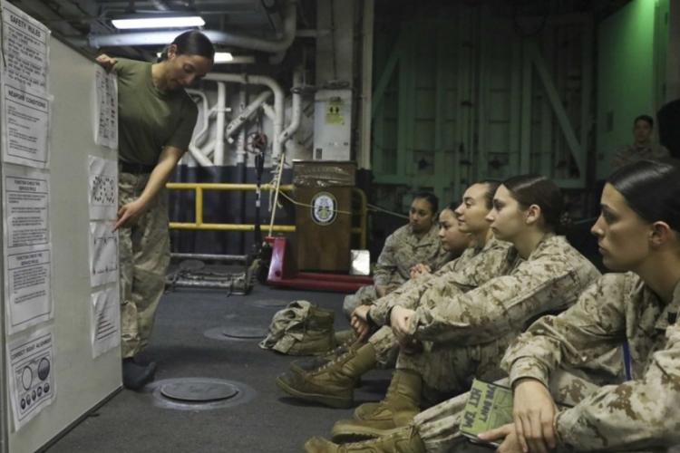 U.S. Marines discuss a female engagement team training schedule on the deck of the Wasp-class amphibious assault ship USS Kearsarge on March 4, 2019. The National Commission on Military, National and Public Service recommended in a report to the Pentagon, White House and Congress that selective service registration should be extended to women. TAWANYA NORWOOD/U.S. MARINE CORPS
