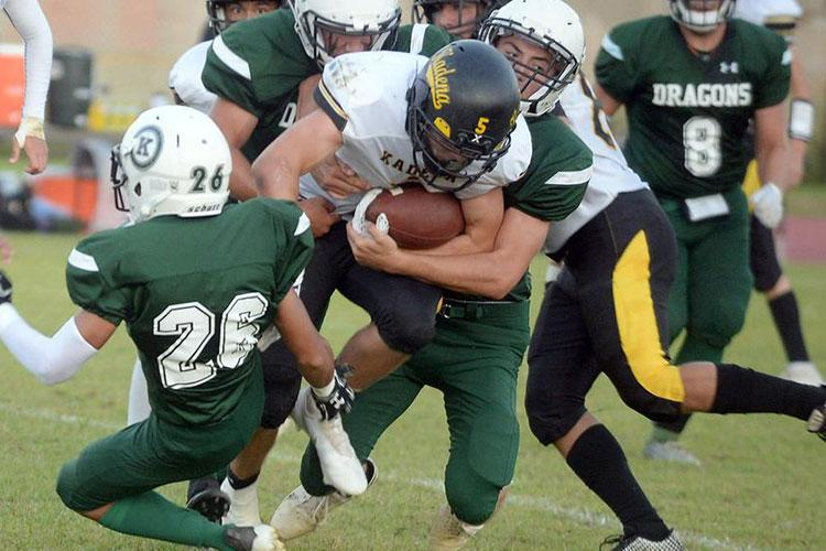 Kadena running back Trent Fowler gets hhemmed in by Kubasaki's Jacob Acosta and Justin Podozon. (Dave Ornauer/Stars and Stripes)