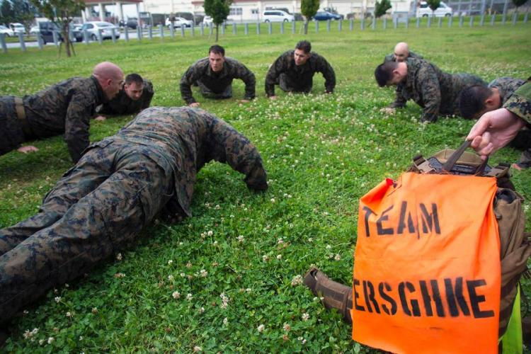 Marines of 3rd Reconnaissance Battalion perform push-ups during the Warrior Challenge. The banner in the foreground identifies the fallen Marine, Sgt. Michael Ferschke, under whose name the team competed at Camp Schwab, Okinawa, March 8, 2019. CARLOS M. VAZQUEZ II/STARS AND STRIPES