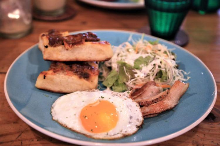 La Polleria Pipeline's morning set is served with a sunny side up egg, bacon, salad, soup, a basic drink and a choice of sweet or savory bread made by Cactus Eatrip. AYA ICHIHASHI/STARS AND STRIPES