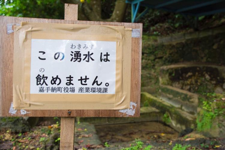 A sign posted by town officials to warn people not to drink nearby polluted spring water is pictured in Kadena, Okinawa, May 10, 2019. STARS AND STRIPES