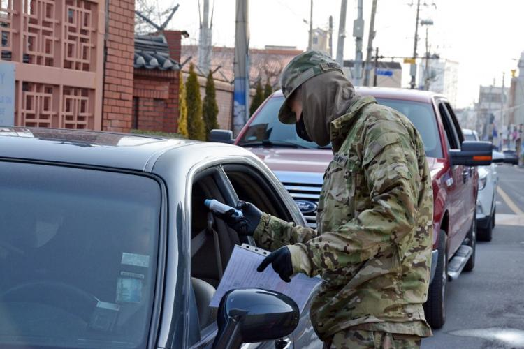Pvt. Hector Mercado, 23, of the 25th Transportation Battalion, checks temperatures before allowing people to enter Camp Walker in the coronavirus-hit city of Daegu, South Korea, Saturday, Feb. 22, 2020. KIM GAMEL/STARS AND STRIPES