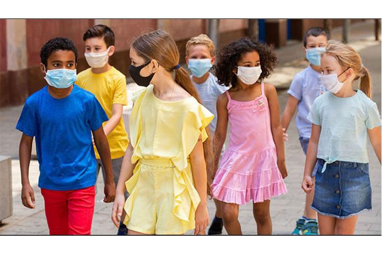 Children wearing face masks for protection against COVD-19 walk on a city street.