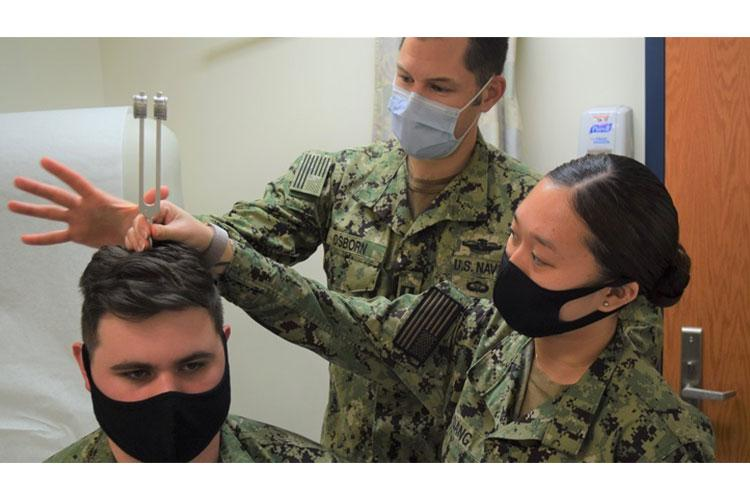 "Navy Lt. Jeffrey Osborn, physician assistant (PA) assigned to Navy Readiness and Training Command Bremerton's Branch Health Clinic Bangor demonstrates to Navy Hospitalmen Wendy Dang (right) and Nicholas Gevedon (seated) the Rinne and Weber test(s) routinely used to evaluate hearing loss. Osborn attests that ""the single best part of his job is training and working with corpsmen. (Photo by Douglas Stutz, NHB/NMRTC Bremerton.)"