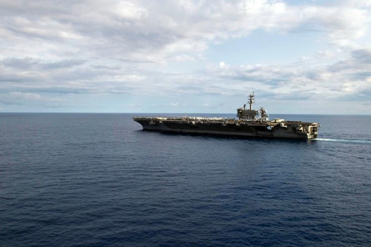 The aircraft carrier USS Theodore Roosevelt steams in the Philippine Sea, March 24, 2020, the same day three sailors were flown from the ship after testing positive for coronavirus. JOMARK ALMAZAN/U.S. NAVY