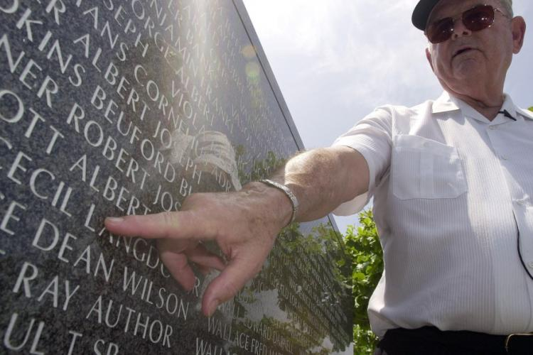 Medal of Honor recipient Robert Bush traces his finger under the name of Albet Walcott at the Cornerstones of Peace Monument in Itoman, Okinawa, June 15, 2003. Walcott was a friend and comrade-in-arms who died during the Battle of Okinawa. STARS AND STRIPES