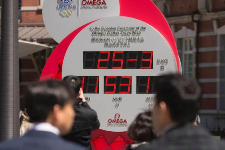 Commuters stop outside Tokyo Station to check out a clock counting down to the Summer Olympics, Wednesday, March 25, 2020. The display was changed to show the current date, 25-3, following a decision to postpone the event because of the coronavirus. AKIFUMI ISHIKAWA/STARS AND STRIPES