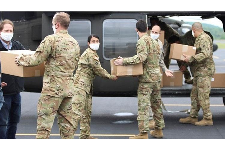 D.C. National Guard soldiers load boxes of medical face masks onto a UH-60 Black Hawk helicopter during an aeromedical support mission in Asheboro, N.C., April 25. (Photo by Army Staff Sgt. Andrew Enriquez, released)